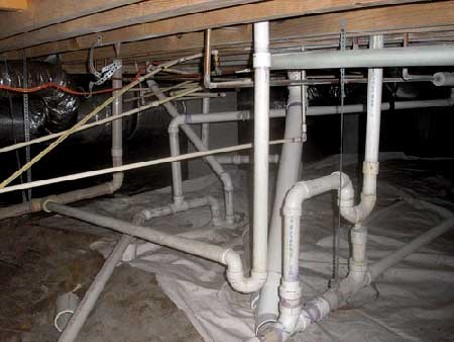 A maze of plumbing in a crawl space
