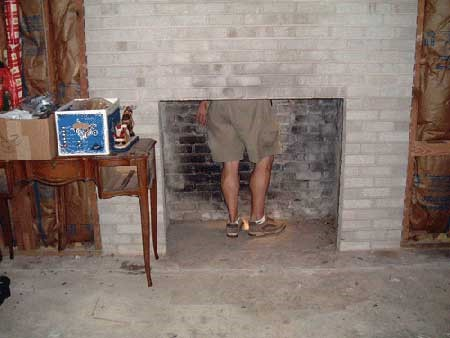 Man in a fireplace inspecting it